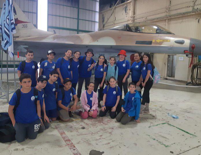 תמונה של הנוער עם מטוס ברקע מאחוריהם